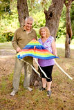 Elderly couple. Happy elderly couple in love flying a kite royalty free stock photography