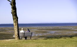 Elderly couple. An elderly couple sitting on a park bench looking out at the sea Stock Photo