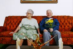 Elderly couple. Old couple sit on a orange vintage sofa.  Man having flowers and the woman is not interested about it Stock Photography