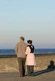 Elderly Couple. Walking together on a seaside promenade Stock Images