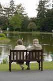 Elderly couple. An elderly couple relax on a park bench royalty free stock photography