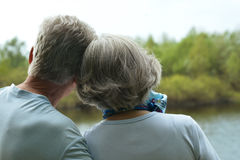Elderly couple admiring the beauty of summer lake Stock Photo