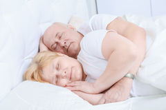 Elderly couple asleep in bed Stock Images