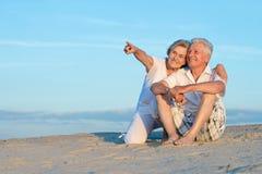 Elderly couple on beach. Elderly couple on the beach enjoy the sea breeze Royalty Free Stock Photo