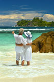 Elderly couple on the beach facing the sea Stock Photos