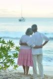 Elderly couple on the beach facing the sea Royalty Free Stock Photos