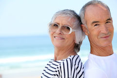 Elderly couple at the beach stock images