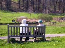 Elderly couple on a bench. Elderly couple sitting on a park bench Royalty Free Stock Image