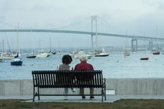 Elderly Couple on Bench Watching Harbor Boats stock photos