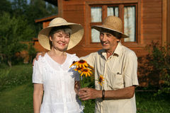 The elderly couple with bouquet of rudbeckia flowers Stock Photography