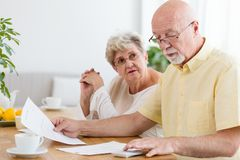Elderly couple calculating costs of household. Senior people wit. H low pension royalty free stock photos