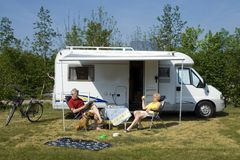 An elderly couple with camper. An elderly couple sitting in front of a camper Royalty Free Stock Image