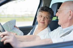 Elderly couple in car with map Royalty Free Stock Photo