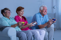 Elderly couple and caregiver playing Royalty Free Stock Images