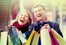 Elderly couple carrying purchases in city Stock Image