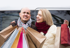 Elderly couple carrying purchases and smiling outdoors Royalty Free Stock Photo