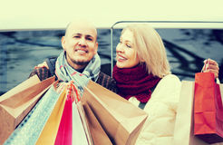 Elderly couple carrying purchases and smiling outdoors Stock Photography