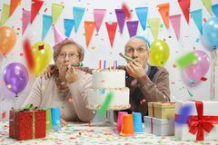 Elderly couple celebrating a birthday with party horns. And a cake royalty free stock photos