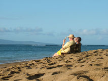 Elderly Couple on Cell Phones. View of an elderly couple on cell phones relaxing on a beach royalty free stock photography