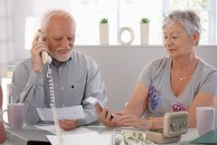 Elderly couple checking bills at home royalty free stock photo