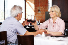 Elderly couple clink glasses Royalty Free Stock Photos