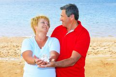 Elderly couple on the coast ,holding corals. Royalty Free Stock Photos