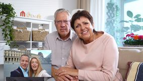 Elderly Couple Connecting with their Adult Children Using Laptop Video Call Camera. Elderly Couple Connecting with their Adult Children on Paris Vacation Using stock footage