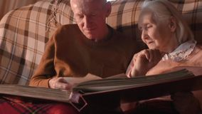 An elderly couple is considering a family photo album wrapped up in a plaid. Golden wedding, happy marriage, grow old together stock footage