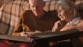 An elderly couple is considering a family photo album wrapped up in a plaid. A married couple of retirement age sitting on a sofa by the fireplace wrapped in a stock video footage