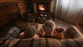 An elderly couple considers a family photo album wrapped in a blanket sitting by a cozy fireplace. Golden wedding, happy marriage, grow old together stock footage
