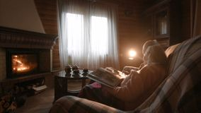 An elderly couple considers a family photo album wrapped in a blanket sitting by a cozy fireplace. Golden wedding, happy marriage, grow old together stock video