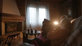 An elderly couple considers a family photo album wrapped in a blanket sitting by a cozy fireplace. Golden wedding, happy marriage, grow old together stock video footage