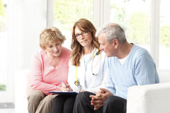 Elderly couple consulting with female doctor Stock Image