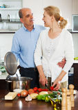Elderly couple cooking Spaniard tomatoes Stock Images