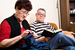 Elderly couple on the couch. Reading and sewing royalty free stock images