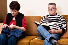 Elderly couple on the couch. Reading and sewing stock photography