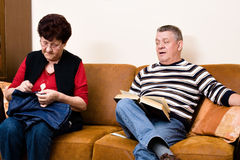 Elderly couple on the couch. Reading and sewing royalty free stock image