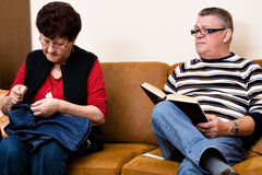 Elderly couple on the couch. Reading and sewing stock image