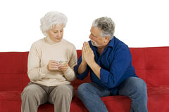 Elderly couple on the couch with money in hand Stock Photos