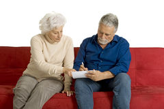 Elderly couple on the couch writing i Royalty Free Stock Images