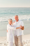 Elderly couple dancing on the beach Stock Images
