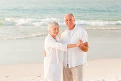 Elderly couple dancing on the beach Stock Photo