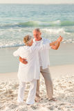 Elderly couple dancing on the beach Royalty Free Stock Photography