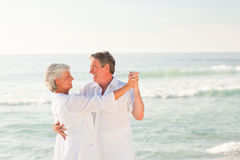 Elderly couple dancing on the beach Stock Photography
