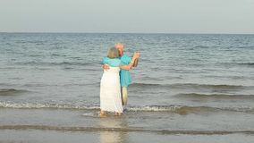 Elderly couple dancing on the beach stock footage
