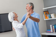 Elderly couple dancing in the living room Royalty Free Stock Photography