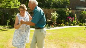 Elderly couple dancing. In their garden stock video