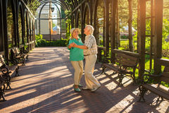 Elderly couple is dancing. Two people in the park. Like in good old times. Waltz on the alley Stock Photo