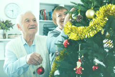 Elderly couple decorate firtree royalty free stock image