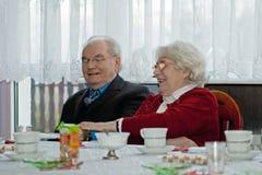 Elderly couple at dinner table. Smiling, elderly couple at a banquet or dinner table Royalty Free Stock Photo